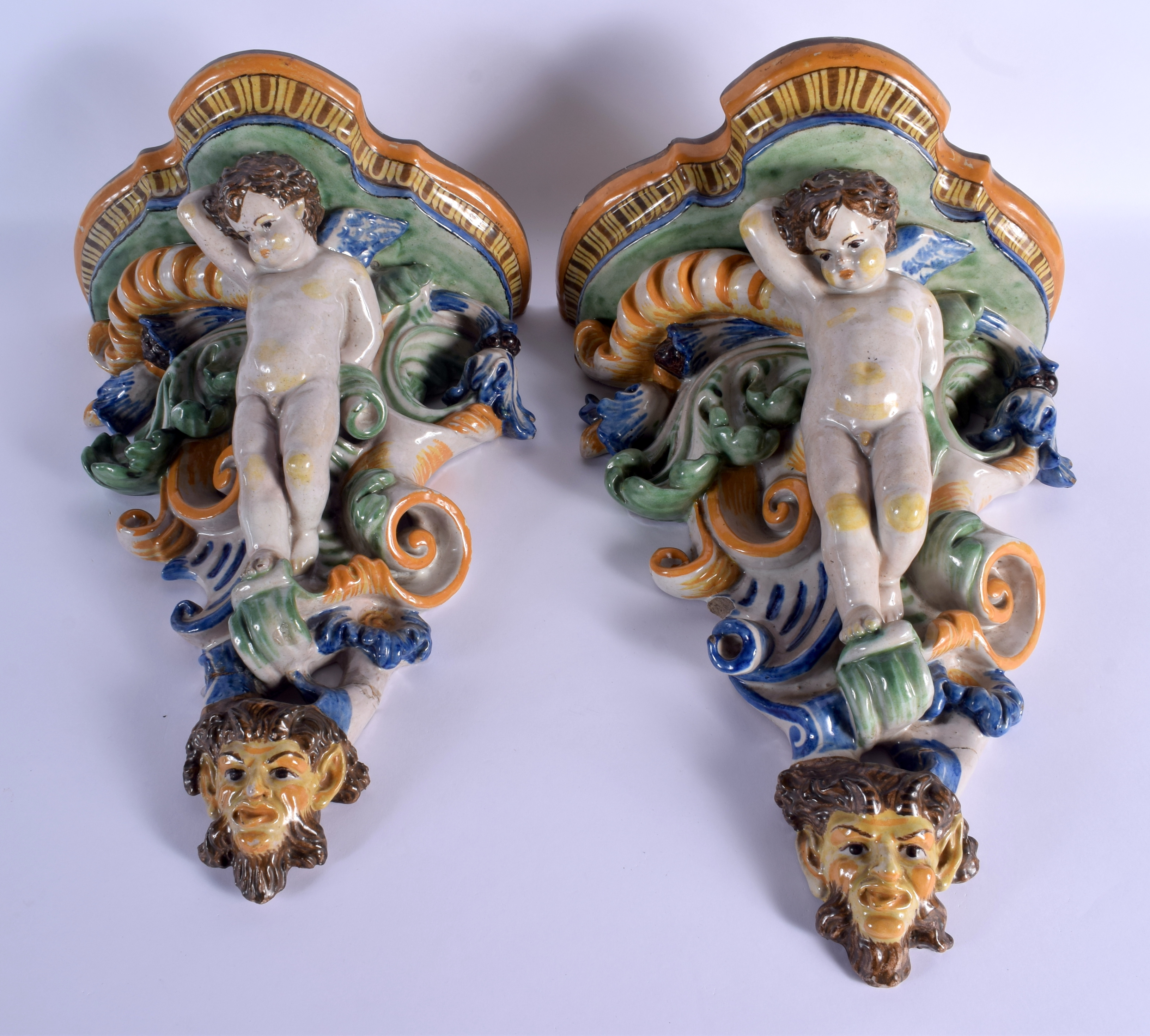 A LARGE PAIR OF 19TH CENTURY ITALIAN MAJOLICA POTTERY WALL BRACKETS formed with figures over mask he