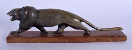 A 19TH CENTURY MIDDLE EASTERN CARVED RHINOCEROS HORN FIGURE OF A ROAMING LION modelled upon a wooden