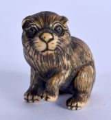 AN EARLY 20TH CENTURY JAPANESE MEIJI PERIOD CARVED IVORY NETSUKE modelled as a dog. 3 cm x 2.75 cm.