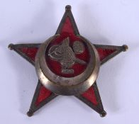 AN UNUSUAL MIDDLE EASTERN BRASS AND ENAMEL STAR BADGE. 4.5 cm wide.