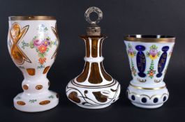 A BOHEMIAN ENAMELLED GLASS GOBLET together with two others. Largest 18 cm high. (3)
