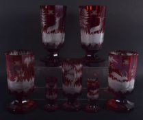 SEVEN ANTIQUE BOHEMIAN RUBY GLASS GOBLET BEAKERS decorated with deer. Largest 18.5 cm high. (7)