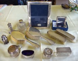 AN ART DECO SILVER DRESSING TABLE SET together with two silver frames, silver topped bottles & jars