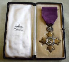 A GEORGE V SILVER GILT CASED OBE MEDAL in original fitted case. Medal 6.5 cm x 4.5 cm.
