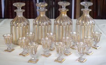 A SET OF FOUR 19TH CENTURY BOHEMIAN CLEAR AND GILDED LIQUOR DECANTERS AND STOPPERS together with mat