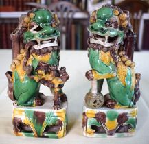 A PAIR OF 17TH CENTURY CHINESE EGG AND SPINACH GLAZED BUDDHISTIC LIONS modelled upon similarly decor