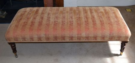 A LONG UPHOLSTERED RED AND GOLD GROUND OTTOMAN. 146 cm x 63 cm.
