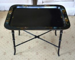 AN ANTIQUE PAPIER MACHE TRAY upon a bamboo type ebonised stand. 77 cm x 50 cm.
