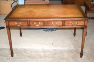 A REPRODUCTION THREE DRAWER LEATHER INSET DESK. 136 cm x 85 cm x 75 cm.