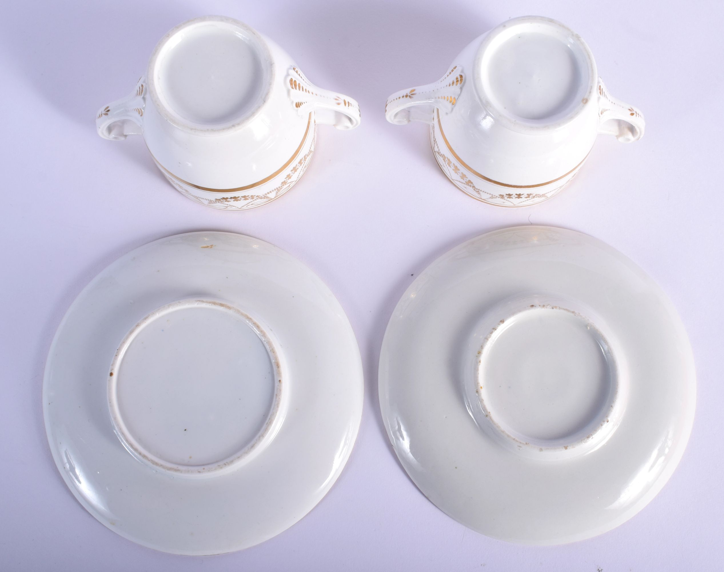 A PAIR OF EARLY 19TH CENTURY TWIN HANDLED GILDED CUPS AND SAUCERS Coalport or Derby, painted with ne - Image 3 of 3