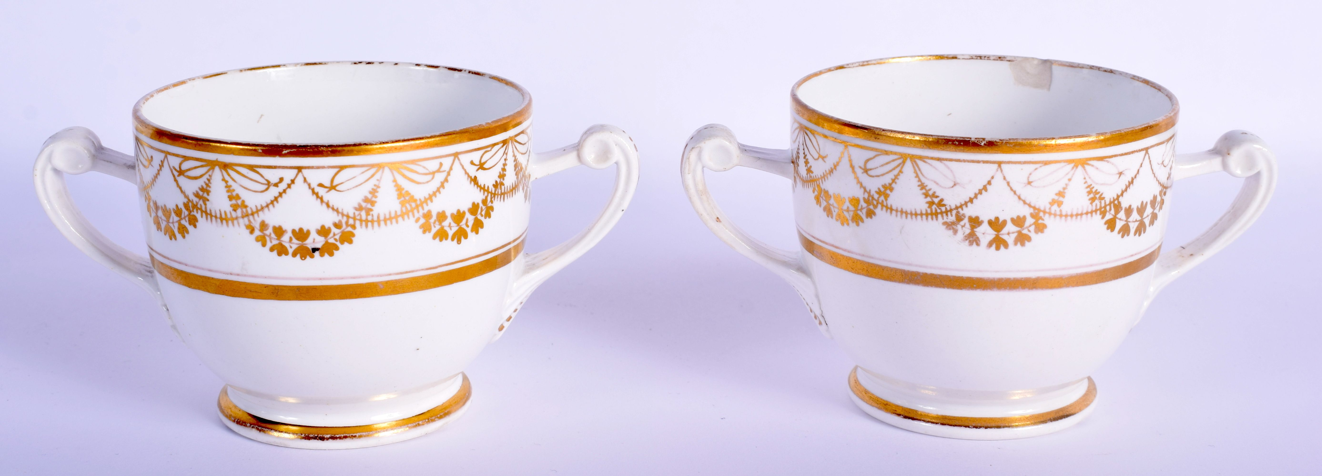 A PAIR OF EARLY 19TH CENTURY TWIN HANDLED GILDED CUPS AND SAUCERS Coalport or Derby, painted with ne - Image 2 of 3
