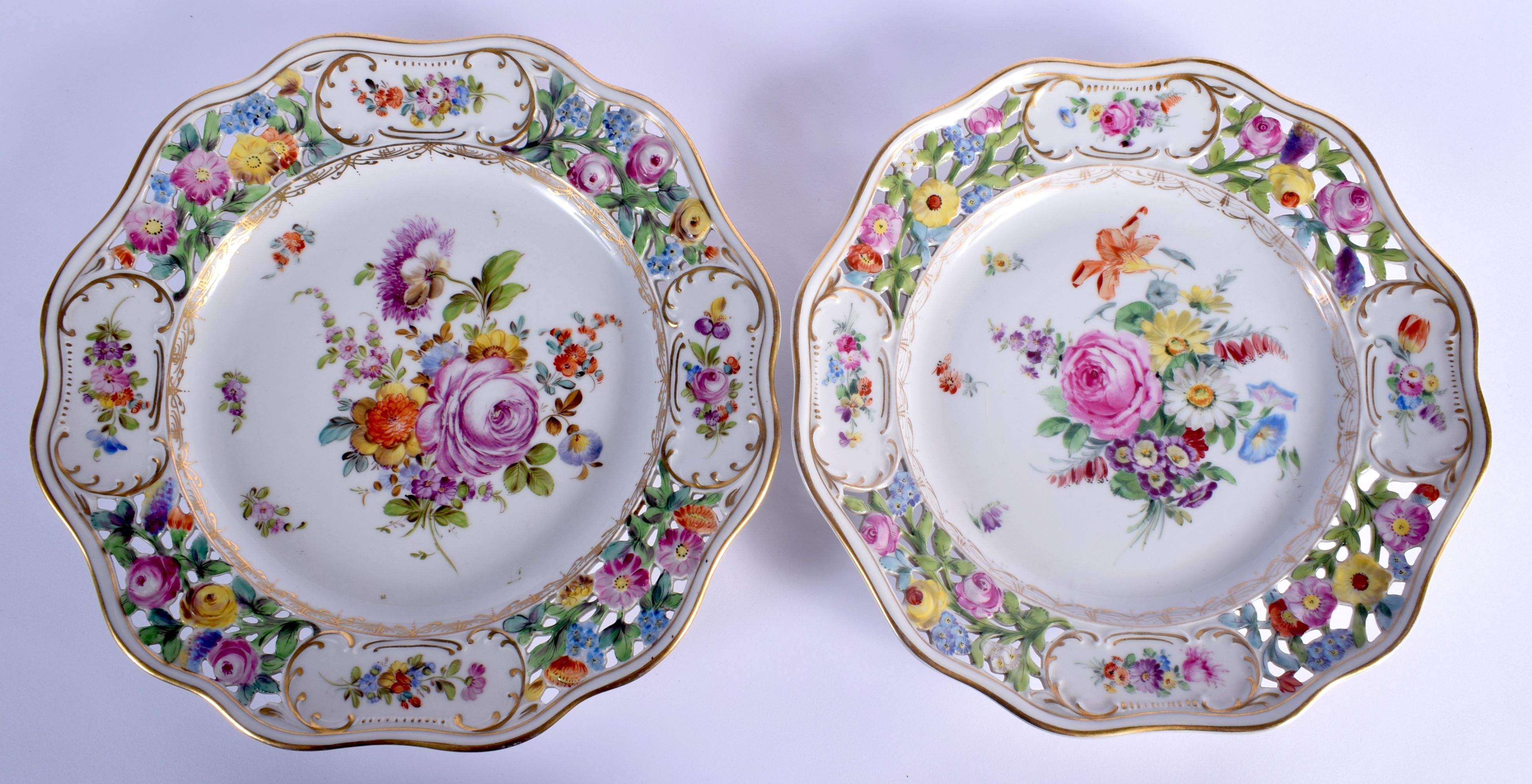 A PAIR OF EARLY 20TH CENTURY DRESDEN RETICULATED PORCELAIN PLATES painted with flowers. 26 cm wide.