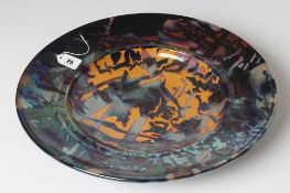 SUTTON TAYLOR (b.1943), a studio pottery charger of dished circular form decorated in abstract
