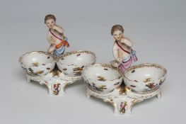 A PAIR OF BERLIN PORCELAIN FIGURAL SALTS, late 19th century, each modelled as a putto standing