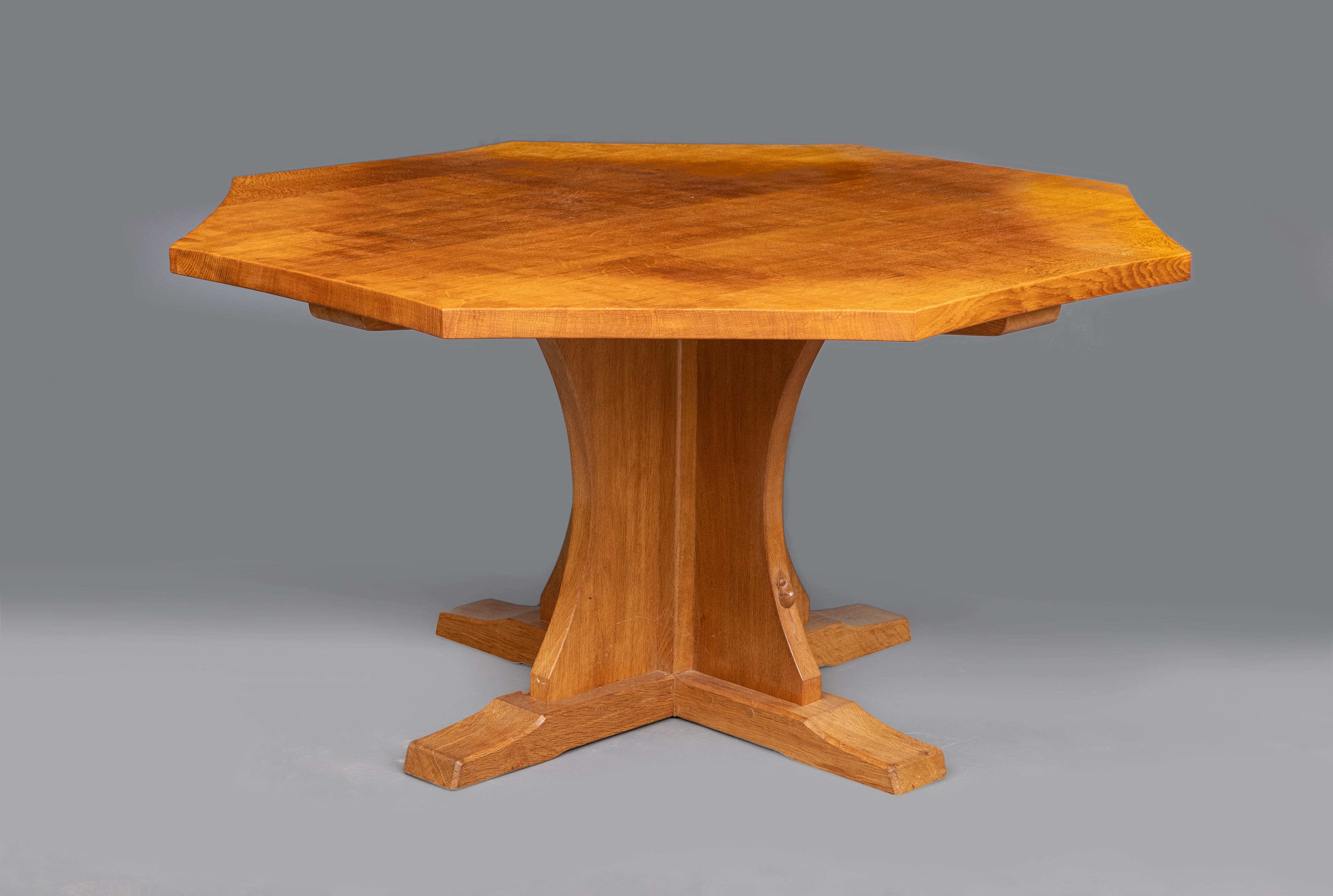 A ROBERT THOMPSON ADZED OAK DINING TABLE, the concave sided octagonal top raised on cruciform