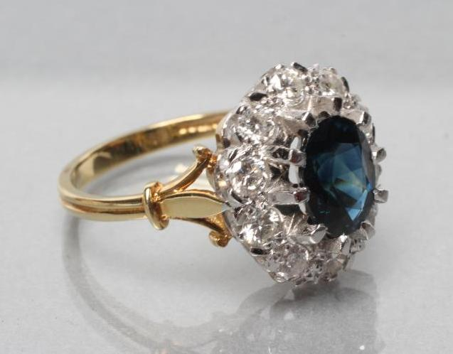 A SAPPHIRE AND DIAMOND CLUSTER RING, the oval facet cut sapphire claw set to a border of ten round