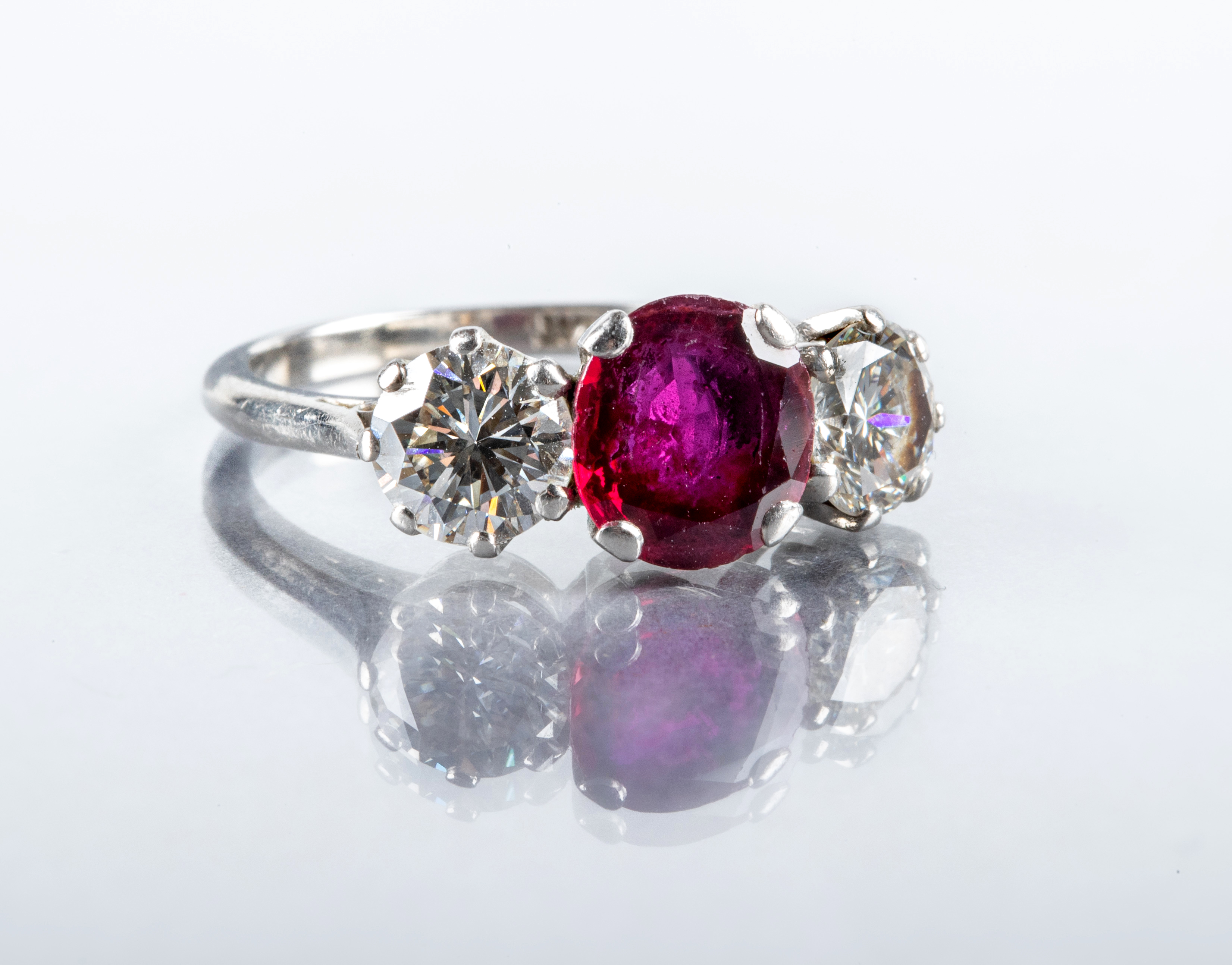 A THREE STONE RUBY AND DIAMOND RING, the circular facet cut ruby claw set and flanked by two