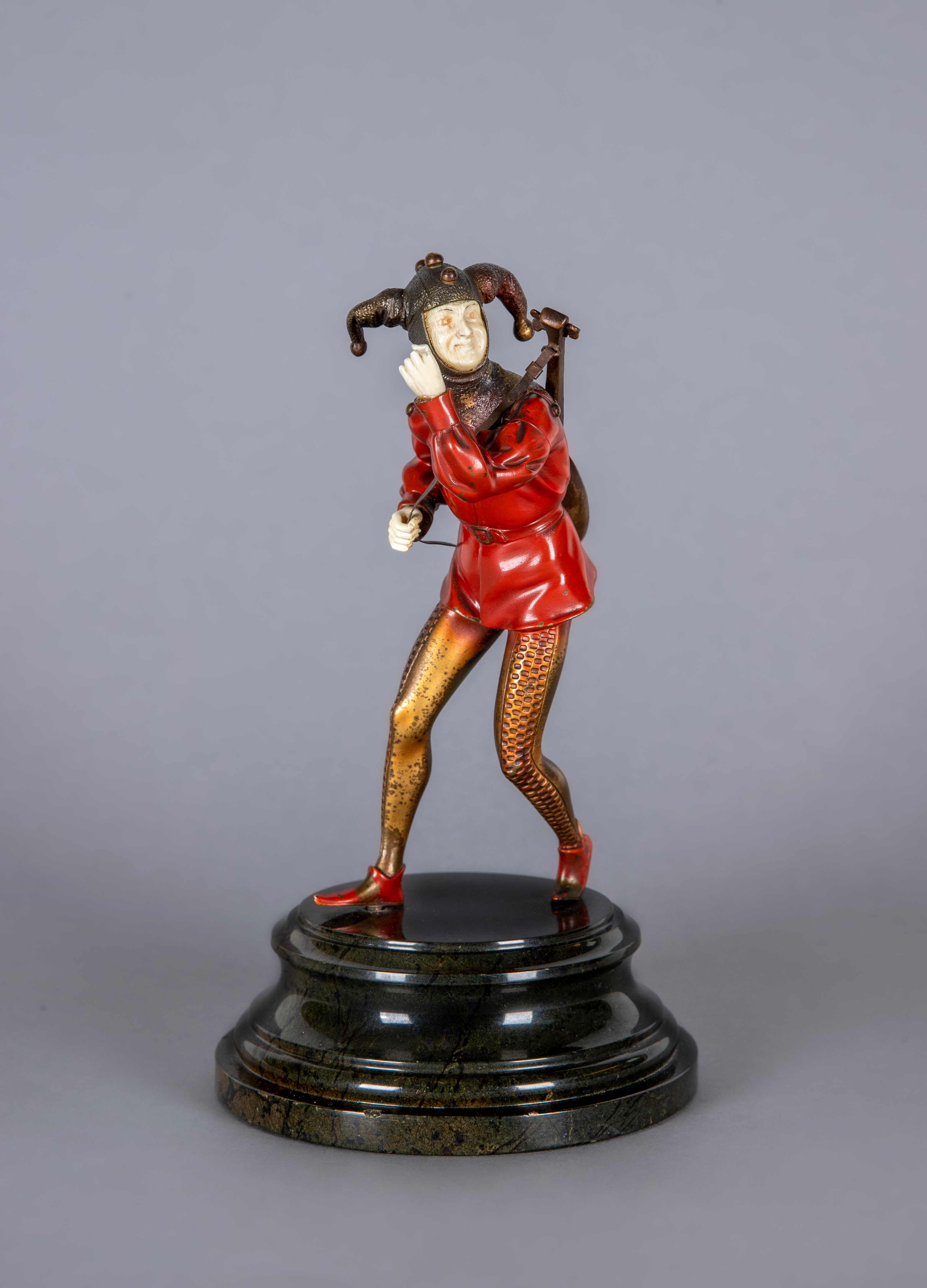 AN ART DECO COLD PAINTED BRONZE FIGURE, cast as a jester wearing red motley with a lute slung over
