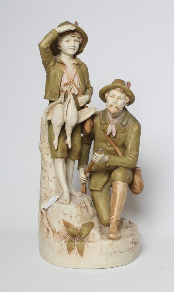A ROYAL DUX FIGURE GROUP, early 20th century, the hunter kneeling and holding a rifle, his young