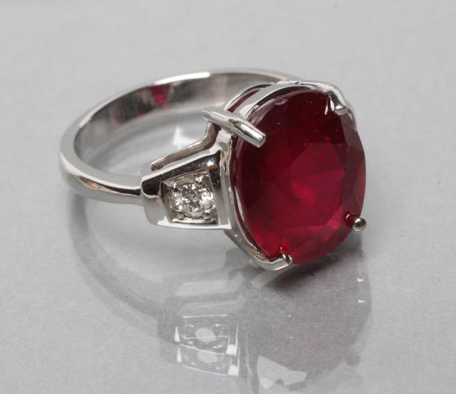 A RUBY RING, the oval facet cut stone of approximately 7.7cts, claw set to shaped shoulders each set
