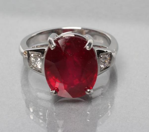 A RUBY RING, the oval facet cut stone of approximately 7.7cts, claw set to shaped shoulders each set - Image 2 of 3