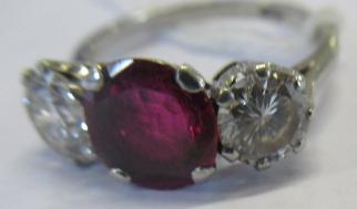 A THREE STONE RUBY AND DIAMOND RING, the circular facet cut ruby claw set and flanked by two - Image 10 of 10