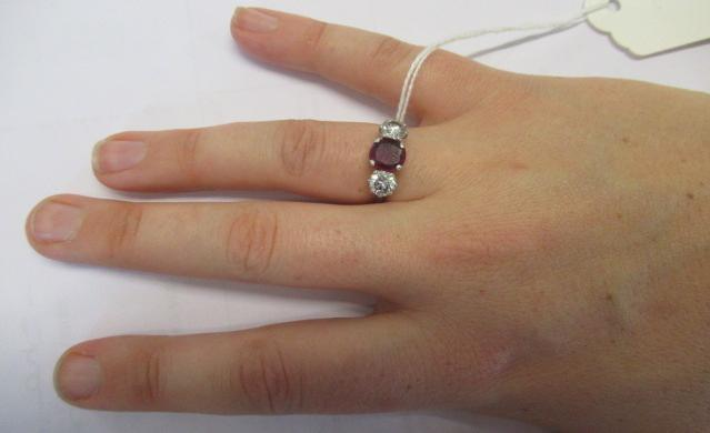 A THREE STONE RUBY AND DIAMOND RING, the circular facet cut ruby claw set and flanked by two - Image 8 of 10