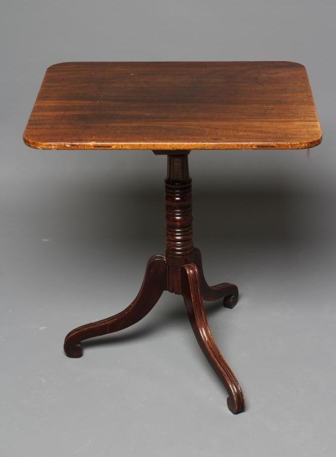 A LATE GEORGIAN MAHOGANY TRIPOD TABLE, early 19th century, the rounded oblong top on ring and