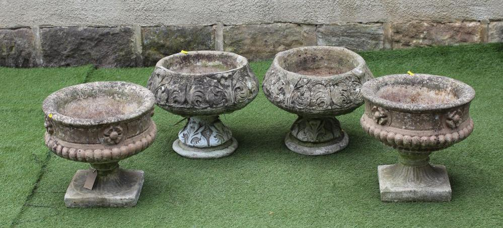 A PAIR OF COMPOSITION STONE URNS, the half fluted circular bowl moulded with flowerheads below a