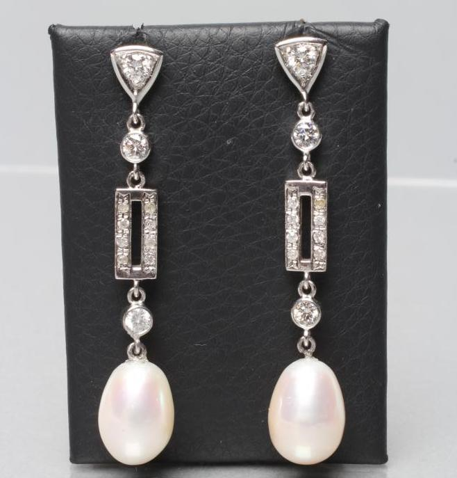 A PAIR OF PEARL AND DIAMOND DROP EAR STUDS, the oval cultured pearls drilled and pendant from shaped