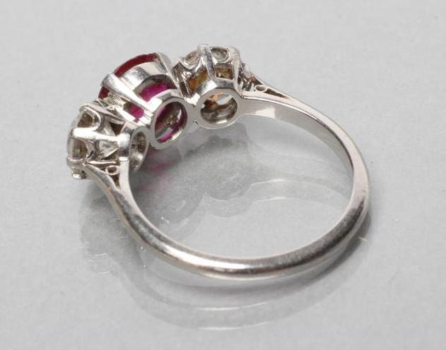 A THREE STONE RUBY AND DIAMOND RING, the circular facet cut ruby claw set and flanked by two - Image 3 of 10