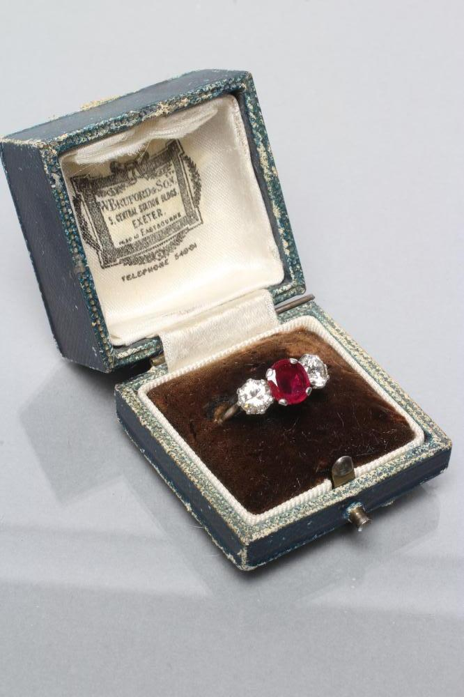 A THREE STONE RUBY AND DIAMOND RING, the circular facet cut ruby claw set and flanked by two - Image 4 of 10