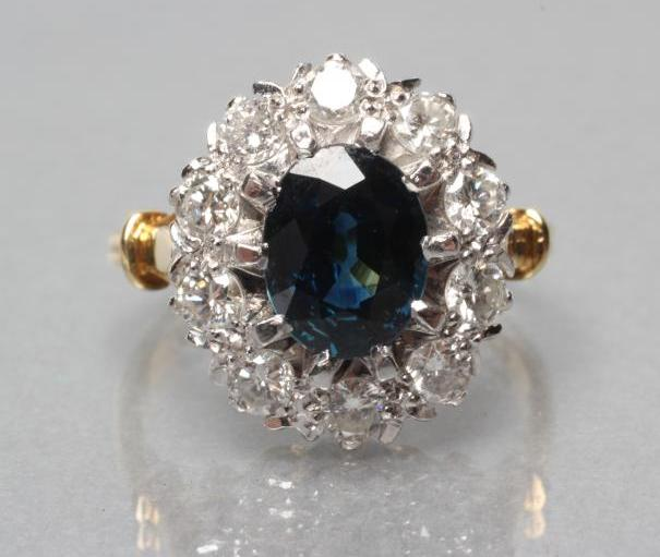 A SAPPHIRE AND DIAMOND CLUSTER RING, the oval facet cut sapphire claw set to a border of ten round - Image 2 of 3