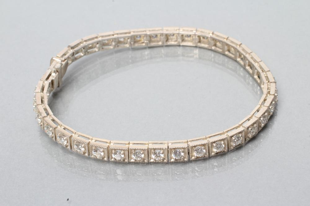 A SILVER TENNIS BRACELET, the thirty six square panels each set with a faceted moissanite,