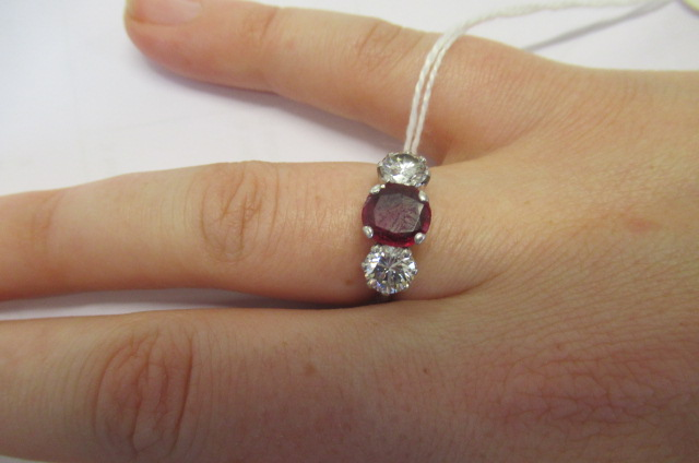 A THREE STONE RUBY AND DIAMOND RING, the circular facet cut ruby claw set and flanked by two - Image 9 of 10