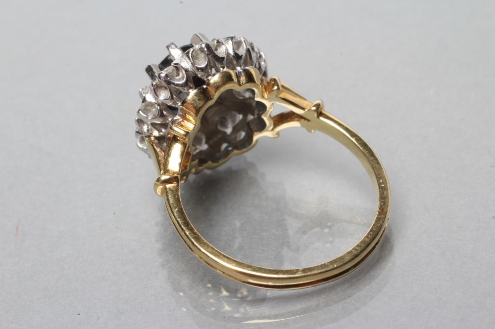 A SAPPHIRE AND DIAMOND CLUSTER RING, the oval facet cut sapphire claw set to a border of ten round - Image 3 of 3