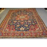 A PERSIAN RUG, the navy blue floral field with similar red and ivory gul, conforming spandrels,