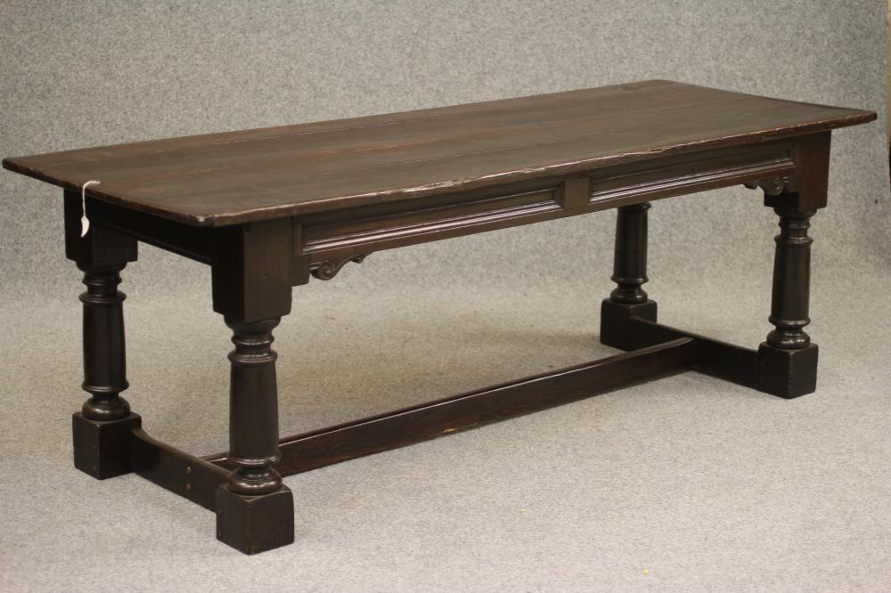 A JOINED OAK REFECTORY TABLE, the cleated plank top over twin panelled moulded frieze with