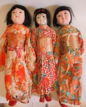 Three large oriental dolls, with composition heads, composition lower limbs, and highly decorative