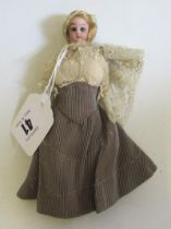 A bisque shoulder head dolls house doll, with brown glass fixed eyes, blond wig, bisque arms,