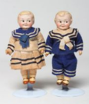 A pair of Armand Marseille googly eyed bisque socket head dolls, with moulded hair and sideways