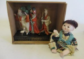 An early 20th century oriental diorama, featuring three papier mache figures on a japanned stand,