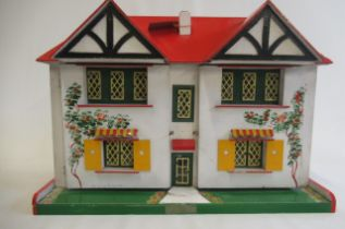 A Triang dolls house, with white walls painted with vines, red roof, metal door, windows and pullout