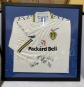 A framed Leeds United football shirt with signatures to include Lucas Radebe and others.Condition