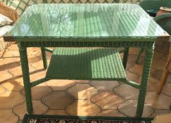A green loom table with glazed top. 61 x 92 x 72cms h.Condition ReportGood condition.