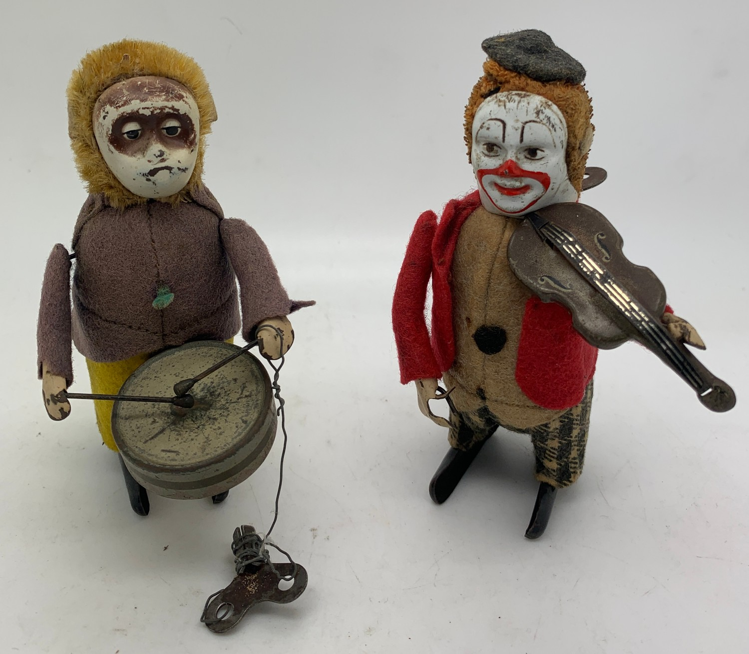 Two Schuco tin plate clockwork musicians, a drummer and a violinist. 11cms h. Working order.