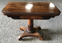 A Regency rosewood fold over card table with green baize, half reeded stem on 4 feet. 91cms w x