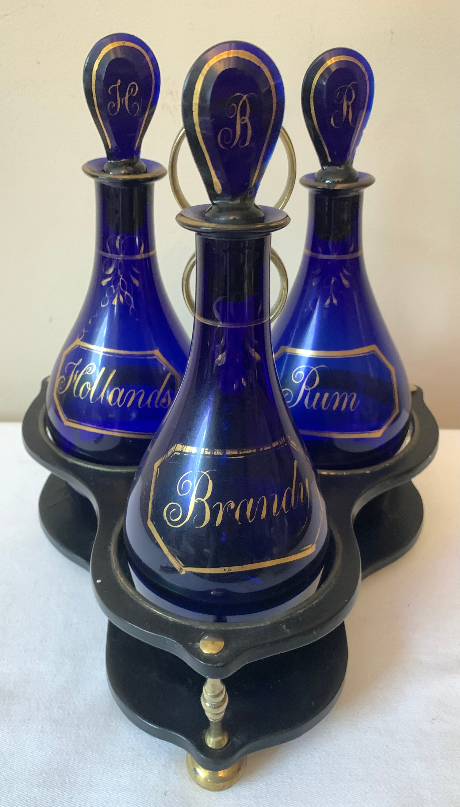 Three early 19thC Bristol Blue bottle decanters on paper mache and brass stand. Comprises of