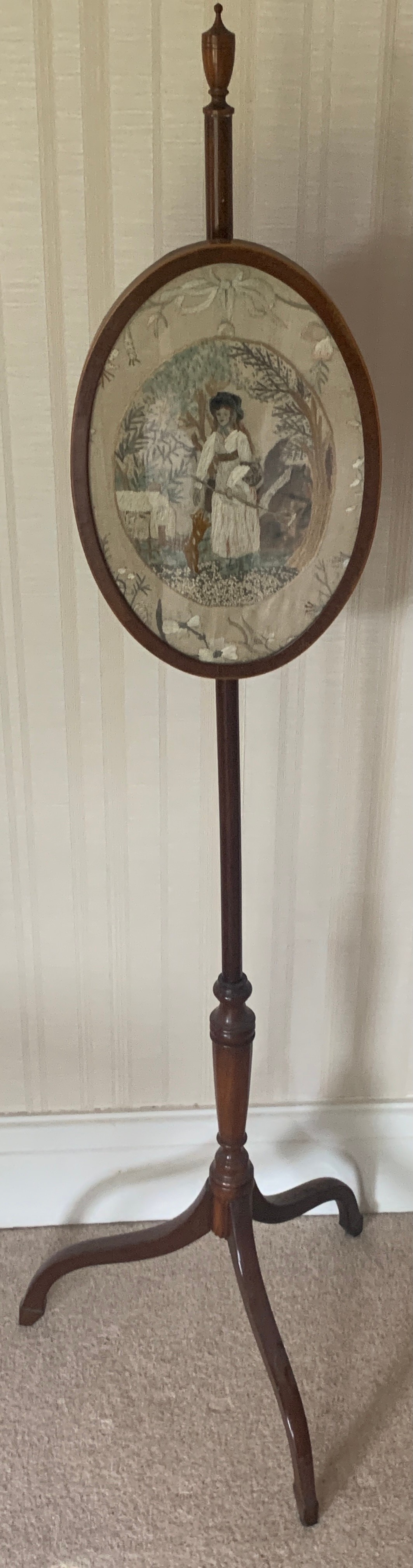 A Victorian mahogany pole screen on tripod base with embroidery to top. 131cms h.Condition