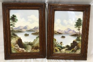 A pair of oak framed hand painted tile plaques of country lake and mountain scenes. Tile size 30.